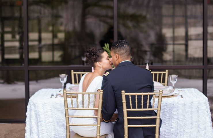 Couple kissing at sweetheart table